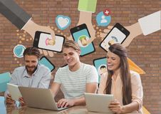 Happy business people at a desk looking at a computer and a tablet against brick wall with graphics Royalty Free Stock Photos