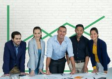 Happy business people at a desk standing against white wall with green graphic Royalty Free Stock Images