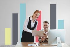 Happy business people at a desk using a tablet against white wall with graphics. Digital composite of Happy business people at a desk using a tablet against Royalty Free Stock Image
