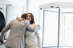 Happy business people embracing at brightly lit convention center Stock Image