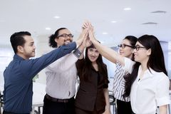Happy business people giving high five while standing in the office.  Royalty Free Stock Photography