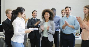 Happy business people group clapping hands congradulating female colleague with good results, cheerful team celebrating