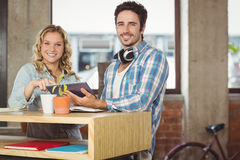 Happy business people holding digital tablet by table in office Royalty Free Stock Photo