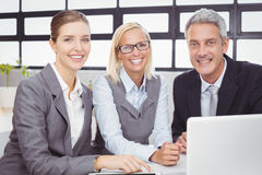 Happy business people with laptop at desk Royalty Free Stock Image