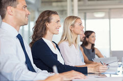 Businesspeople attend at seminar. Happy business people listening to explanations at seminar in office boardroom. Business team during a meeting. Happy young Royalty Free Stock Images