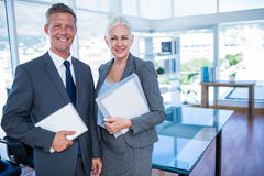 Happy business people looking at camera and holding shield Stock Images