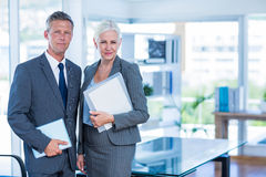 Happy business people looking at camera and holding shield Royalty Free Stock Photo