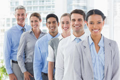 Happy business people looking at camera in a row. In office royalty free stock photo