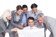 Happy business people looking at newspaper Stock Photo