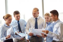 Happy business people with papers talkig in office Royalty Free Stock Image