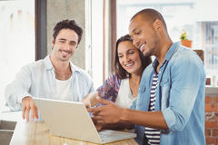 Happy business people pointing towards laptop in office Royalty Free Stock Images