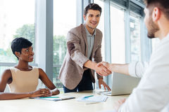 Happy business people shaking hands in office Stock Image