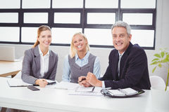 Happy business people sitting with client at desk Royalty Free Stock Photos
