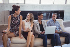 Happy business people sitting together on sofa while holding technologies Royalty Free Stock Photos