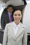 Happy Business People Standing By Airplane Stock Photography