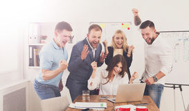 Happy business people team celebrate success in the office. Happy business people celebrate success looking at laptop screen in the office. Successful corporate Royalty Free Stock Photography