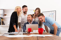 Happy business people team together have fun in office. Happy business people laugh near laptop in the office. Successful corporate team of female and male Stock Photos