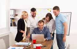 Happy business people team together have fun in office. Happy business people laugh near laptop in the office. Successful corporate team of female and male Royalty Free Stock Photos