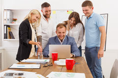 Happy business people team together have fun in office. Happy business people laugh near laptop in the office. Successful corporate team of female and male Stock Image