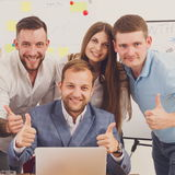 Happy business people team together near laptop in office Stock Images