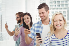 Happy business people using smartphones while standing in row Stock Images