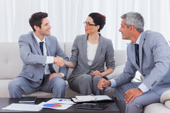 Happy business people working and talking together on sofa Royalty Free Stock Image