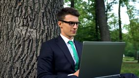 Happy business person enjoying laptop work in green park freedom and inspiration. Stock photo stock photography