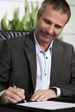 Happy business person signing a contract. Smiling businessman in dark suit and blue shirt sitting at office desk and signing a contract, looking at signature stock images