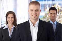 Happy business team. Standing in office, focus on smiling young businessman looking at camera Royalty Free Stock Images