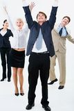 Happy business team. Are standing and raising hands upwards Royalty Free Stock Photos