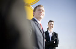 Happy Business Team. Over the shoulder view of business team outside with giant yellow object in background royalty free stock photo