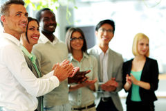 Happy business team applauding. Group of a happy business team applauding Royalty Free Stock Images