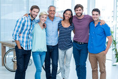 Happy business team with arms around in office Stock Image