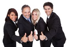 Happy business team celebrating a success. With thumbs up on white background Stock Image