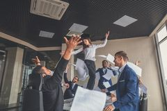 Happy business team celebrating victory in office. woman stand on table Stock Photo