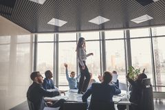 Happy business team celebrating victory in office. woman stand on table Royalty Free Stock Photography