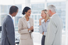 Happy business team chatting and laughing Stock Image