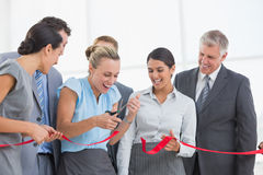 Happy business team cutting red ribbon Stock Photo