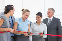 Happy business team cutting red ribbon Royalty Free Stock Photos