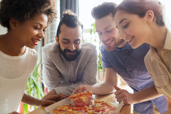 Happy business team eating pizza in office. Business, food, lunch and people concept - happy business team eating pizza in office royalty free stock photo