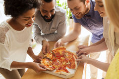Happy business team eating pizza in office. Business, food, lunch and people concept - happy business team eating pizza in office stock image