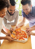 Happy business team eating pizza in office Stock Images