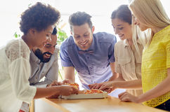 Happy business team eating pizza in office Stock Photo