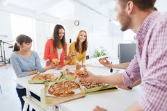 Happy business team eating pizza in office. Business, food, lunch and people concept - happy international business team eating pizza in office royalty free stock photo