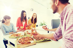 Happy business team eating pizza in office. Business, food, lunch and people concept - happy international business team eating pizza in office stock photography