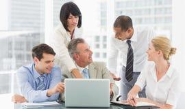Happy business team gathered around laptop talking Royalty Free Stock Image