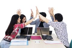 Happy business team gives high five hands together. Group of business team looks happy while giving high five hands together after meeting in the studio royalty free stock images