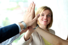 Happy business team giving high five in office.  Stock Images