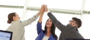 Successful businesswomen motivate each other with High Five. Happy business team giving high five in office stock photo