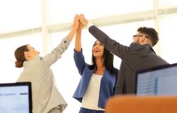 Successful businesswomen motivate each other with High Five. Happy business team giving high five in office stock images